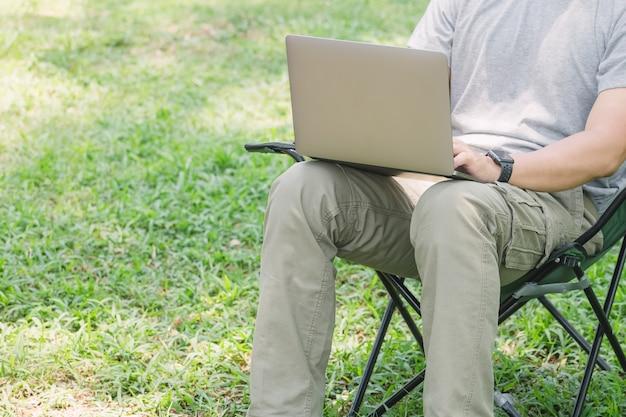 Hombre sentado en la silla de camping y trabajando con una computadora portátil en el jardín Foto Premium