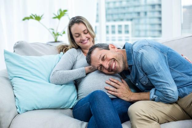 Hombre sentado en el sofá y escuchando el estómago de la mujer embarazada Foto Premium