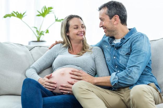 Hombre sentado en el sofá y sosteniendo el estómago de la mujer embarazada Foto Premium