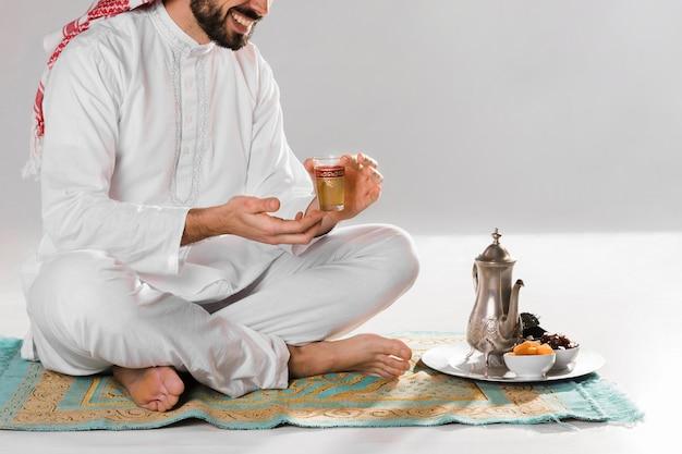 Hombre sentado y sosteniendo una taza de té árabe Foto gratis