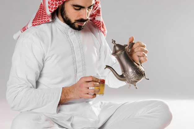 Hombre sentado y vertiendo té árabe en taza Foto gratis