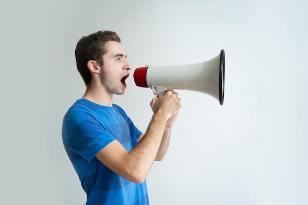 Hombre serio sosteniendo megáfono y gritando en él Foto gratis