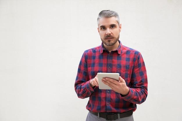 Hombre serio con tableta digital mirando Foto gratis