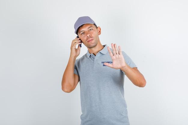 Hombre de servicio técnico hablando por teléfono sin gesto en camiseta gris con gorra Foto gratis