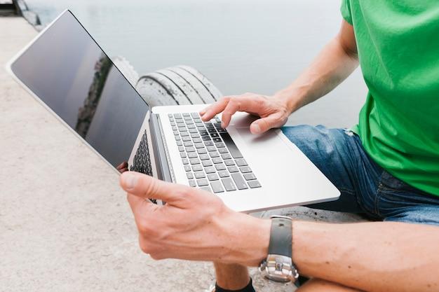 Hombre de sideview que trabaja en la computadora portátil Foto gratis