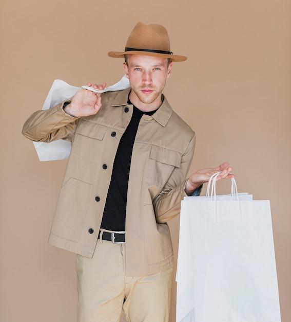Hombre con sombrero marrón sosteniendo las bolsas de la compra. Foto gratis