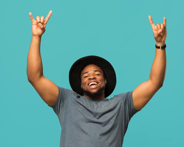 Hombre con sombrero signo de rock and roll Foto gratis