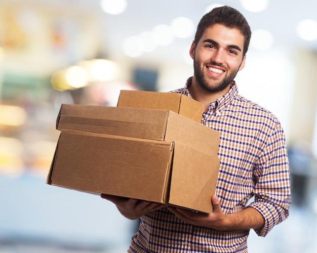 hombre sonriendo cargando cajas descargar fotos gratis