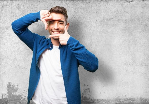 Hombre sonriendo mientras hace un marco con sus dedos Foto gratis