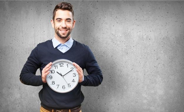Hombre sonriendo con un reloj grande Foto gratis