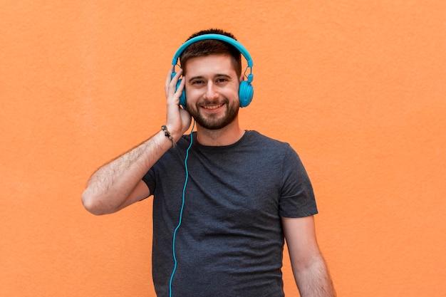 Hombre sonriente con auriculares azules Foto gratis