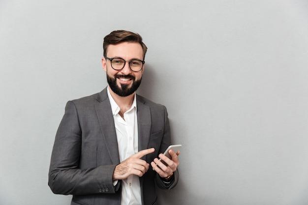 Hombre sonriente en camisa blanca escribiendo mensajes de texto o desplazamiento de alimentación en la red social con teléfono inteligente sobre gris Foto gratis