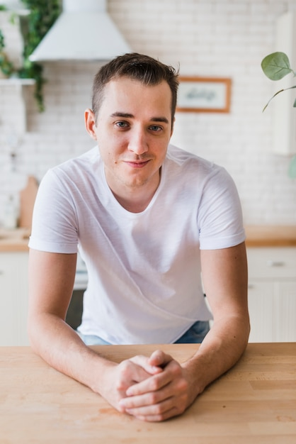 Hombre sonriente en la camiseta blanca que se sienta en la cocina Foto gratis