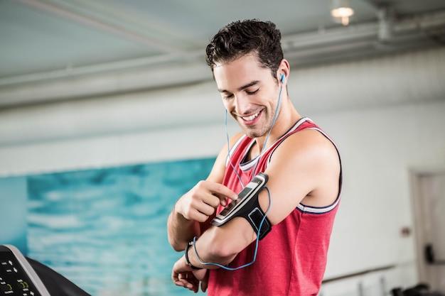 Hombre sonriente en la cinta con teléfono inteligente en el gimnasio Foto Premium