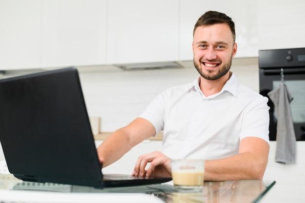 Hombre sonriente en cocina con laptop en frente Foto gratis