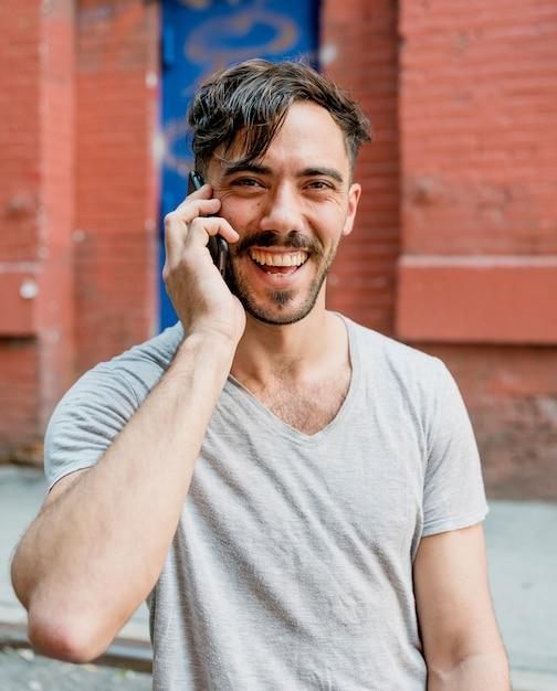 Hombre sonriente hablando por teléfono Foto gratis