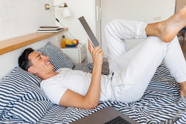 Hombre sonriente joven en traje de pijama casual sentado en la cama en la mañana con tableta, autónomo en casa Foto gratis