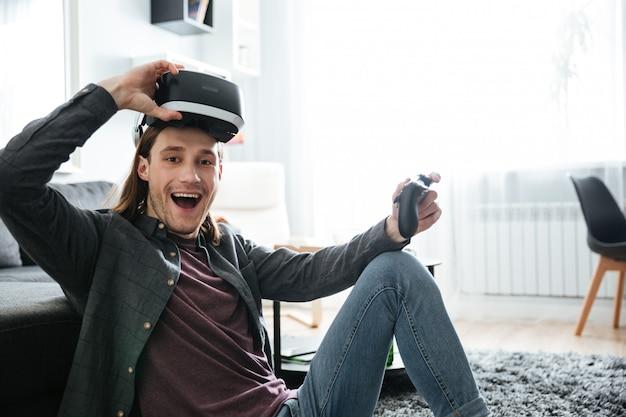 Hombre sonriente jugar juegos con gafas de realidad virtual 3d Foto gratis