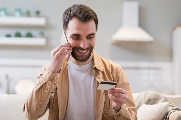 Hombre sonriente ordenando en línea mientras habla por teléfono Foto gratis