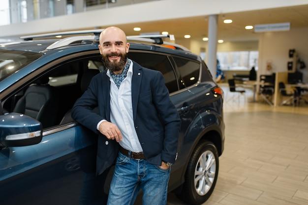 Hombre sonriente posa en automóvil en concesionario de automóviles. Foto Premium