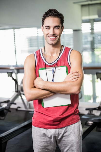 Hombre sonriente que se coloca con el tablero y el cronómetro en el gimnasio Foto Premium