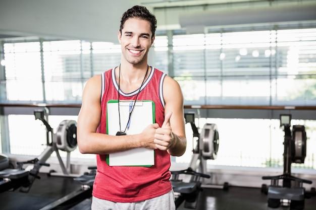 Hombre sonriente que se coloca con el tablero y el cronómetro y que muestra el pulgar para arriba en el gimnasio Foto Premium