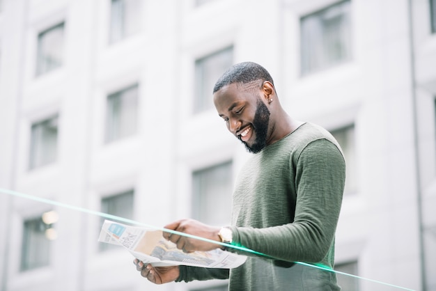 Hombre sonriente que lee el periódico cerca de la cerca de cristal Foto gratis