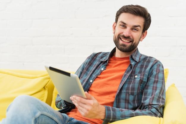 Hombre sonriente que sostiene una tableta Foto gratis