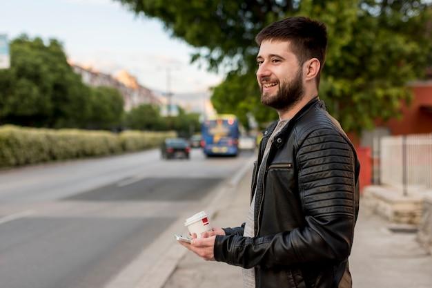 Hombre sonriente que sostiene la taza y el smartphone Foto gratis