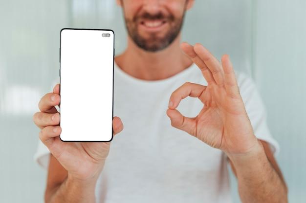 Hombre sonriente que sostiene el teléfono con maqueta Foto gratis