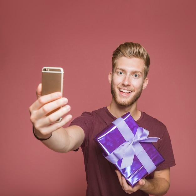 Hombre sonriente que toma el autorretrato del móvil que sostiene la caja de regalo Foto gratis