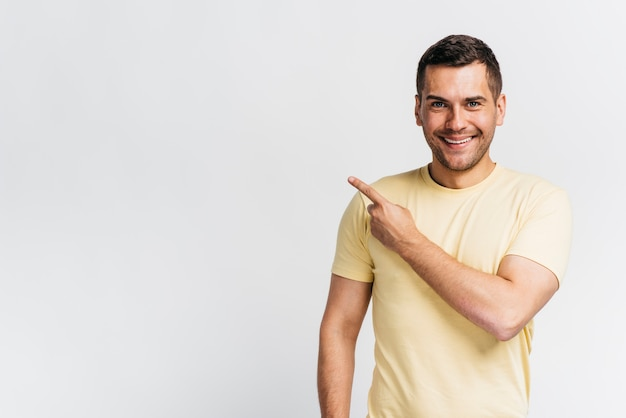 Hombre sonriente señalando con espacio de copia Foto gratis