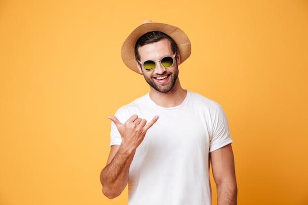 Hombre sonriente en sombrero de verano mirando cámara aislada gesticular Foto gratis