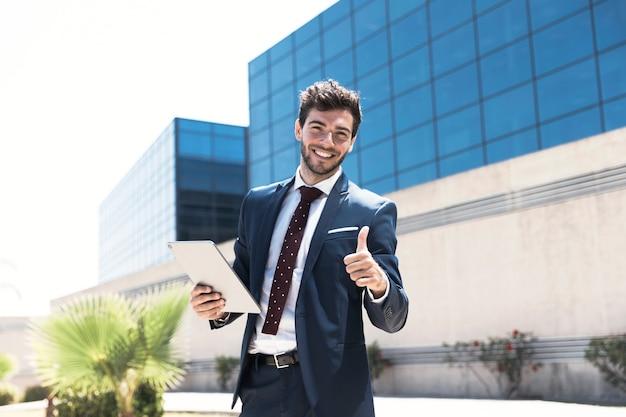 Hombre sonriente con tableta mostrando aprobación Foto gratis