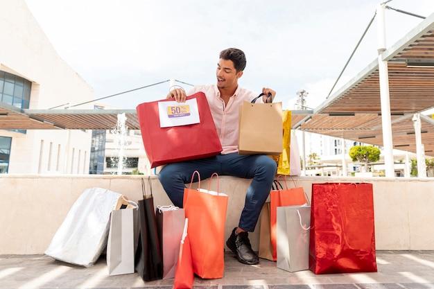 Hombre sorprendido mirando bolsas de compras Foto gratis