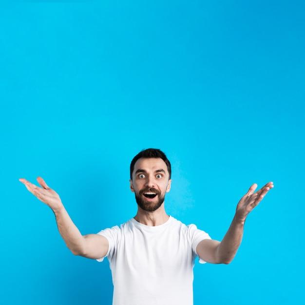Hombre sorprendido posando con los brazos abiertos Foto gratis