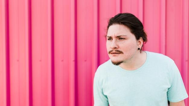Hombre sospechoso de pie contra la hoja de metal corrugado rosa Foto gratis