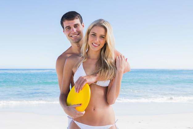 Hombre sosteniendo un disco volador y abrazando a su novia Foto Premium