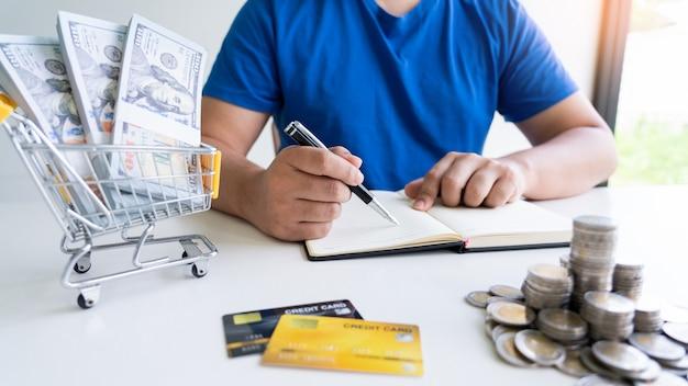 Hombre sosteniendo facturas y contando dinero con pluma de gastos diarios del hogar Foto Premium
