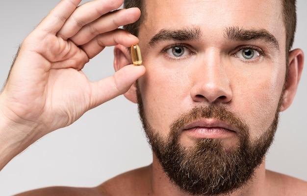 Hombre sosteniendo una pastilla junto a su rostro Foto gratis