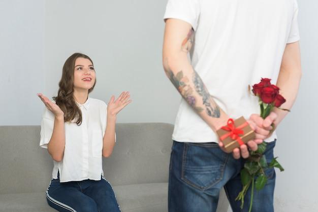 4f485b11c8be Hombre sosteniendo regalos para mujer joven detrás de la espalda ...
