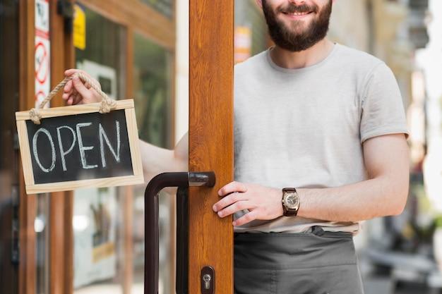 Hombre sosteniendo somos signo abierto Foto Premium