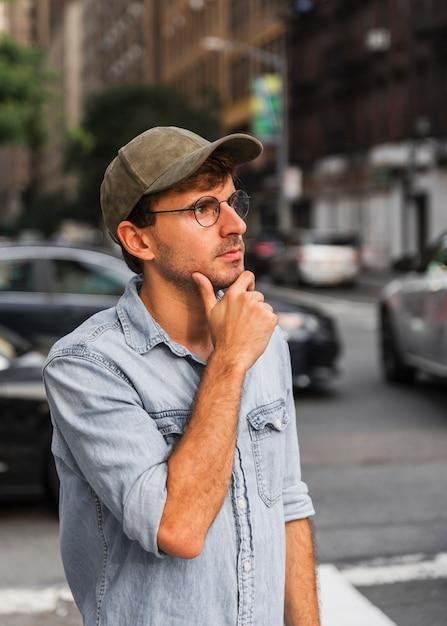 Hombre sosteniendo su mano debajo de su barbilla Foto gratis
