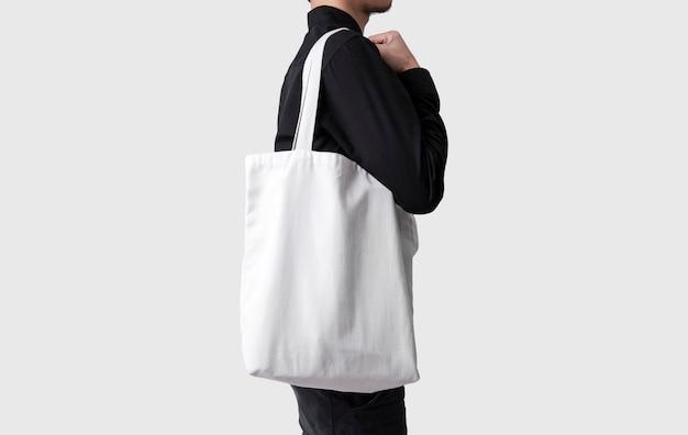 El hombre está sosteniendo la tela de la lona del bolso para la plantilla del espacio en blanco de la maqueta aislada en fondo gris. Foto Premium