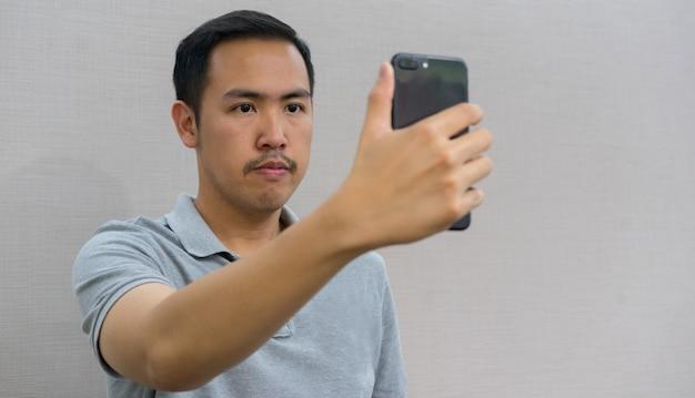 Hombre sosteniendo un teléfono inteligente y utilizando la tecnología de reconocimiento de escaneo facial para desbloquear y acceder Foto Premium