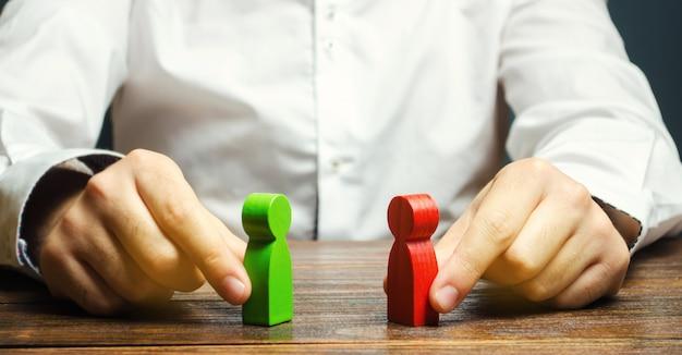 Un hombre sostiene en sus manos la figura roja y verde. Foto Premium