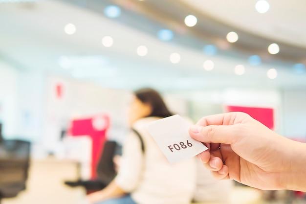 El hombre sostiene la tarjeta de espera mientras espera en el área de recepción moderna Foto gratis