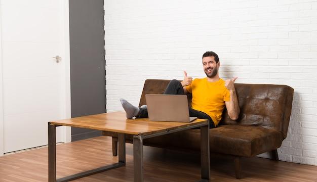Hombre con su computadora portátil en una habitación dando un pulgar hacia arriba gesto con ambas manos y sonriendo Foto Premium