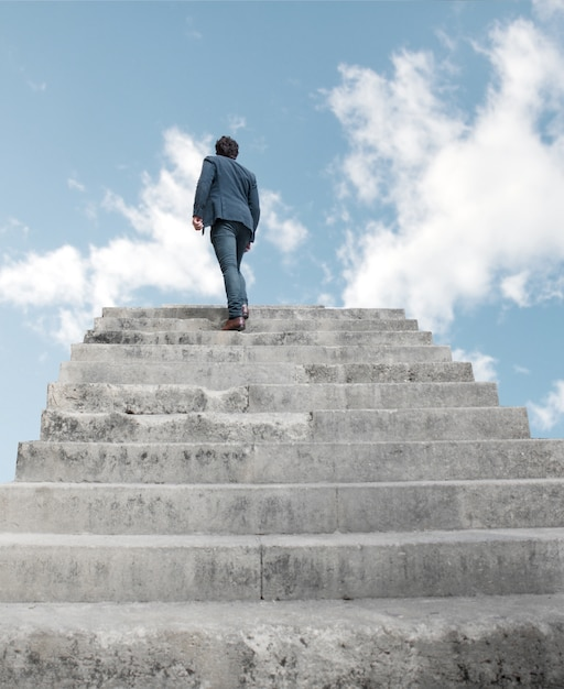 Hombre subiendo por escaleras al cielo Foto gratis