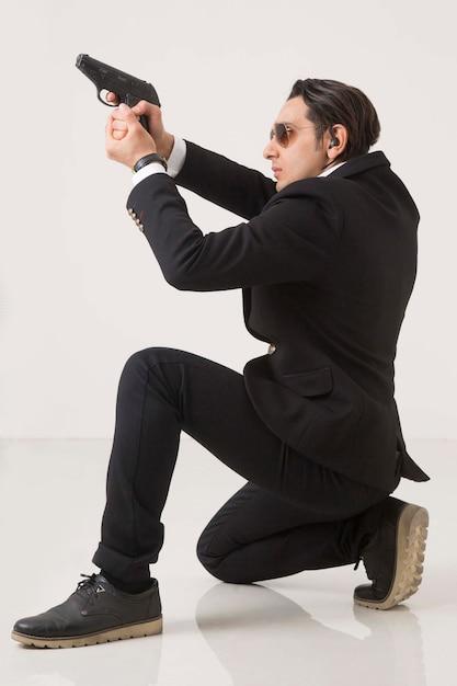 Hombre en suite de negocios y pistola sobre fondo blanco, disparando y sentado sobre fondo blanco. Foto gratis